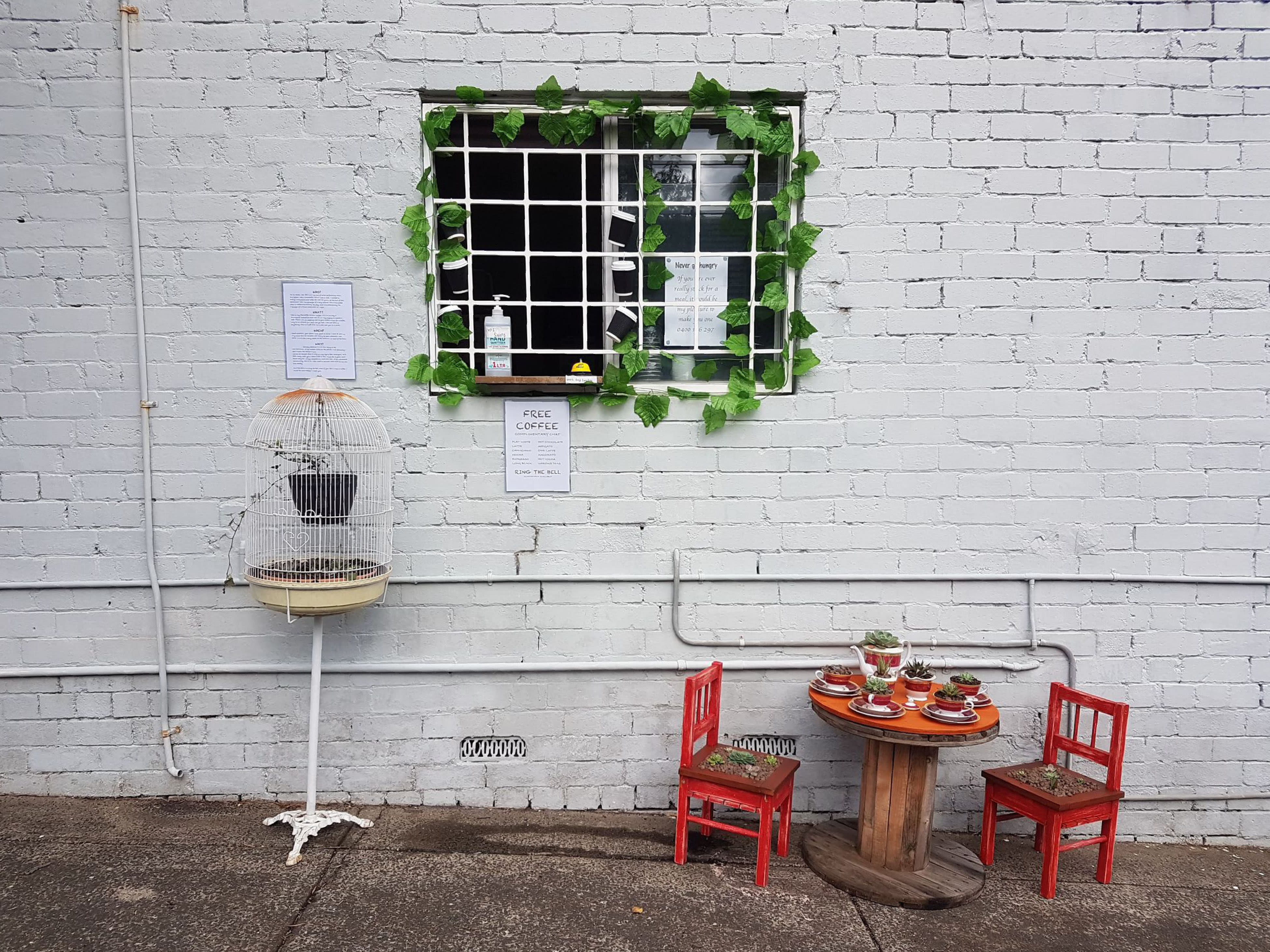 In this July 25, 2020 photo provided by Rick Everett, a small table decorated with succulents sits below a window where Everett offers free coffee and conversation to friends and neighbors at his home in Sydney, Australia, during the coronavirus pandemic. (Rick Everett via AP)