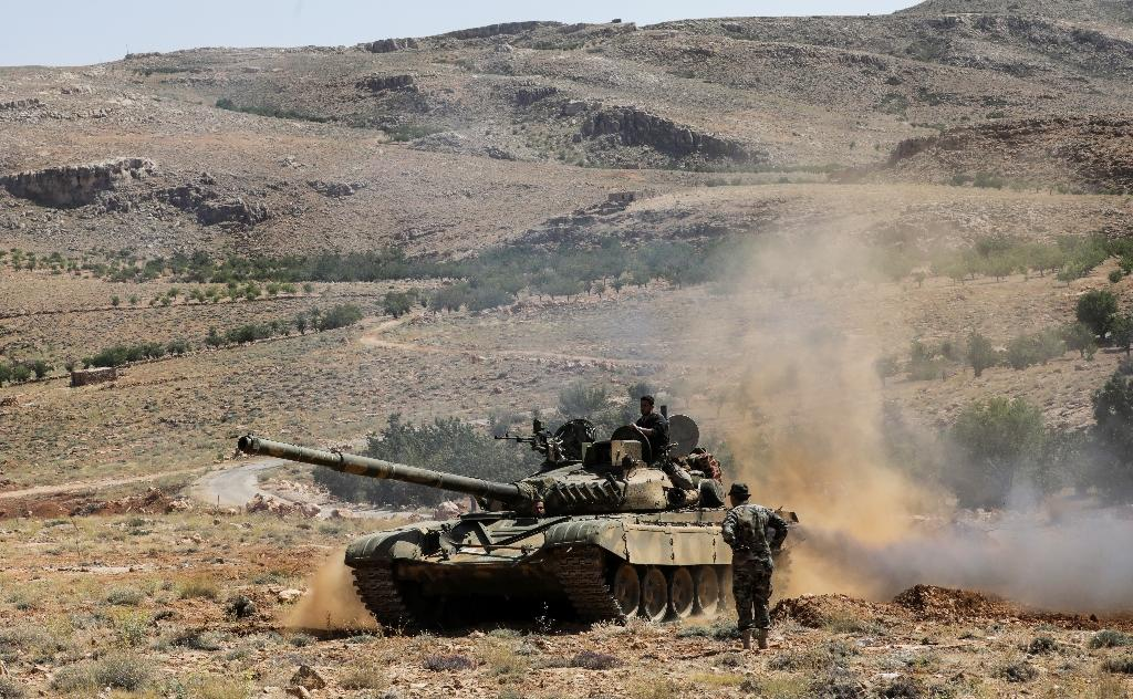 A picture taken on July 26, 2017 during a tour guided by the Lebanese Shiite Hezbollah movement shows Syrian soldiers riding on a tank near Hezbollah fighters in a mountainous area around the Lebanese town of Arsal along the border with Syria (AFP Photo/ANWAR AMRO)