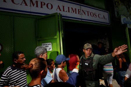 A Venezuelan soldier tries to control the crowd as people queue to buy food outside a market in Caracas, Venezuela July 19, 2016. REUTERS/Carlos Garcia Rawlins