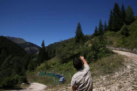 Ramiz Selimaj, 53, points towards the border with Montenegro from his village of Haxhaj, Kosovo, August 28, 2016. REUTERS/Hazir Reka