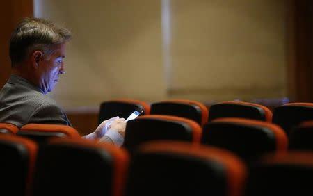 Brazilian tycoon Eike Batista checks his mobile phone before his court hearing in Rio de Janeiro