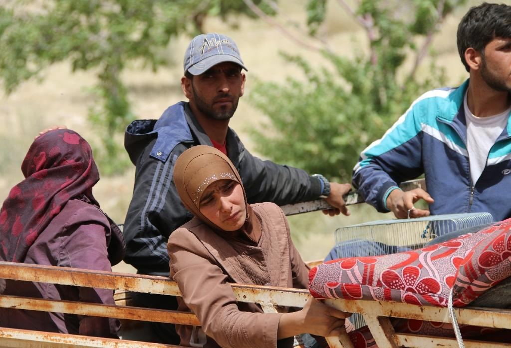 (FILES) Syrian refugees are seen on the back of a pick up truck in the eastern Lebanese border town of Arsal (AFP Photo/STRINGER)