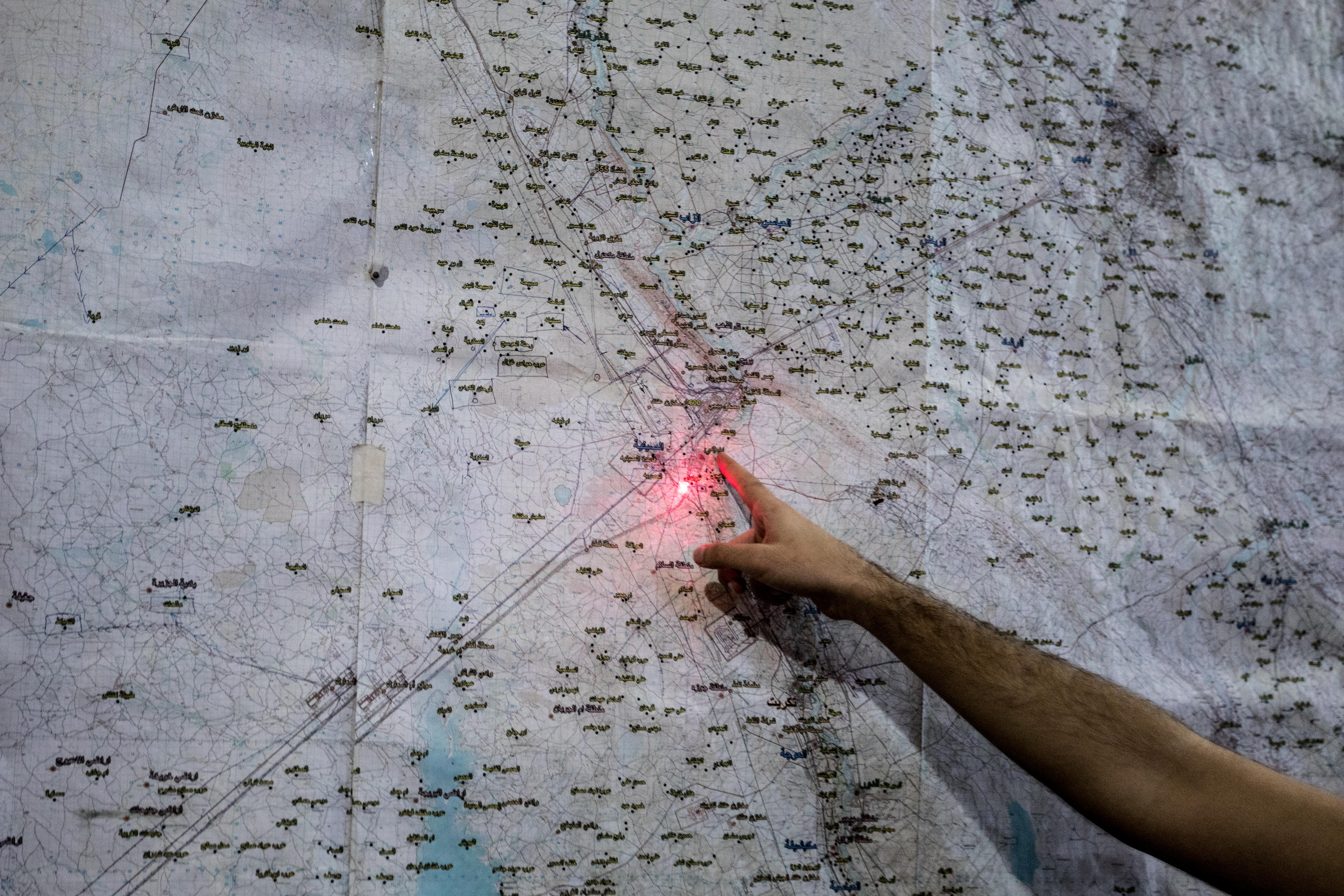 <p><em><strong>Baiji, Iraq  </strong></em> At headquarters, Hajji Imad Karim al-Shahmani, commander of the Shiite Hashed al-Shaabi units in Baiji, outlines details of his strategies in the fight against ISIS on a military map. (Photo: Sebastian Backhaus) </p>