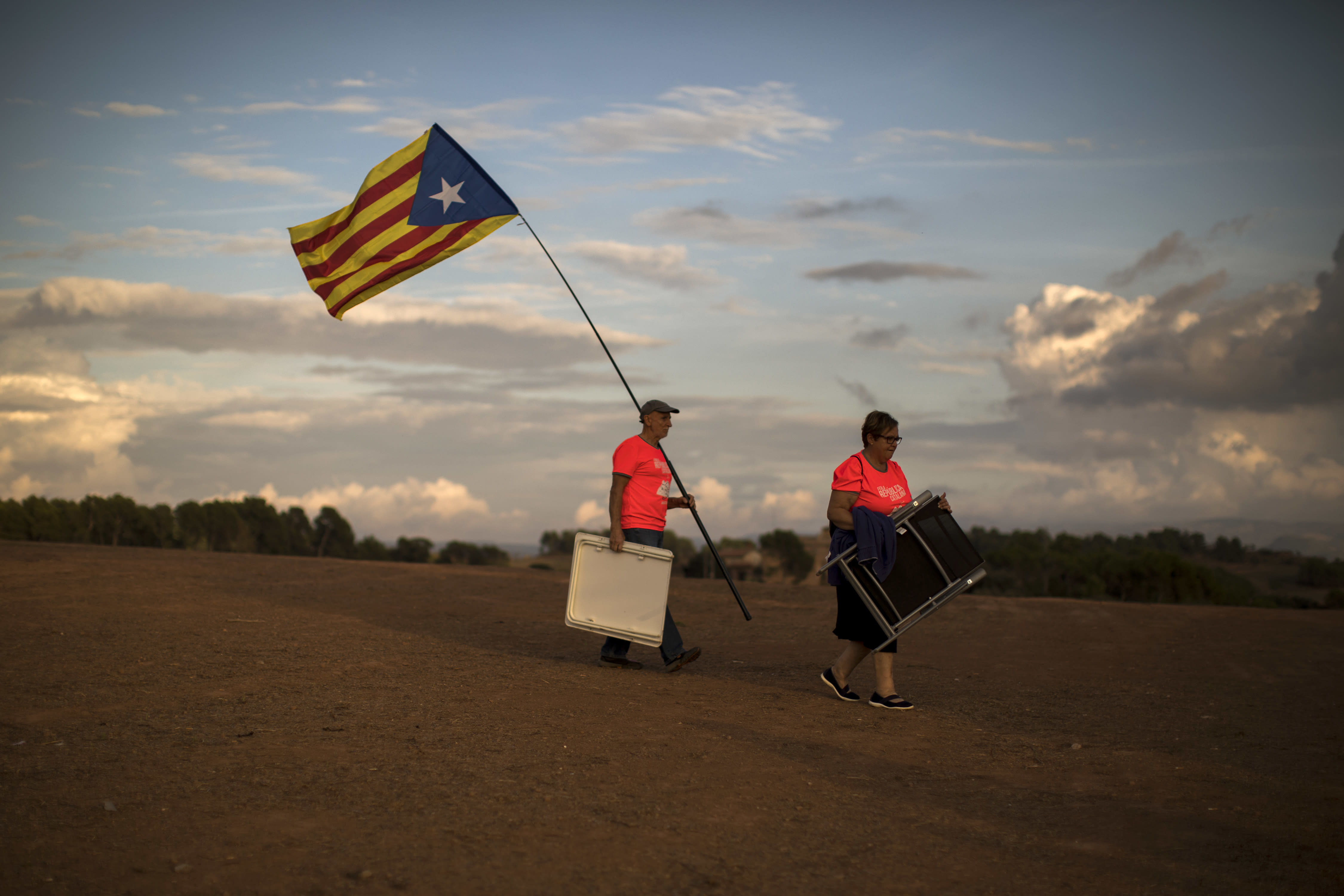 In this Tuesday, Sept. 18, 2018 photo, pro independence people carry chairs and a picnic basket, as they arrive to a field overlooking the Lledoners prison in Sant Joan de Vilatorrada, about 50 kilometres away from Barcelona, Spain. Every Tuesday as the sun sets on the quiet hills surrounding the Lledoners prison in rural Catalonia, dozens of people sit in a field overlooking the penitentiary where seven out of the nine prominent jailed separatists are awaiting trial for their involvement in an unauthorized referendum on independence held last year. (AP Photo/Emilio Morenatti)