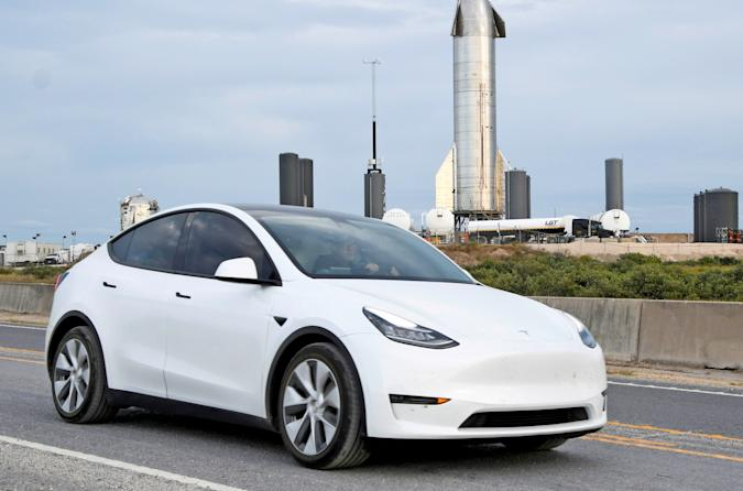 A white Tesla on the highway with the SpaceX Starship in the background.