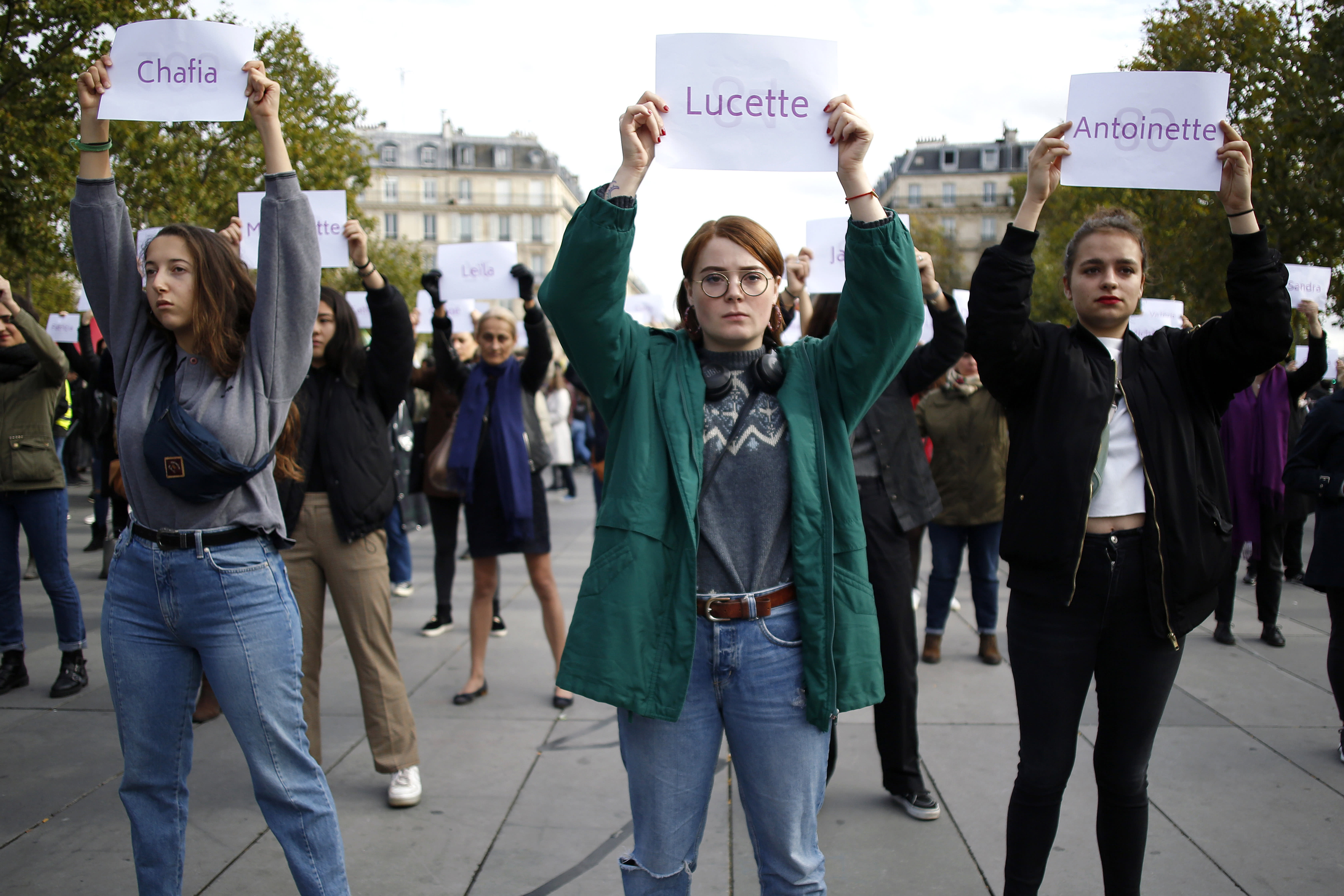 FILE - In this Oct.19, 2019 file photo, women hold placards with the names of women killed by their partners, during a protest, in Paris. A French government commission examining domestic violence is recommending that authorities now confiscate firearms from individuals following the first complaint of family violence levied against them. In France, a woman is killed by her partner every three days, according to government statistics. (AP Photo/Thibault Camus, File)