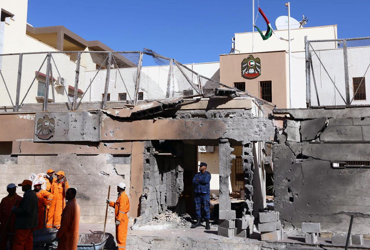 Municipality workers clean up the debris as Libyan security forces inspect the scene of a car bombing outside the UAE embassy in Tripoli on November 13, 2014 (AFP Photo/Mahmud Turkia)