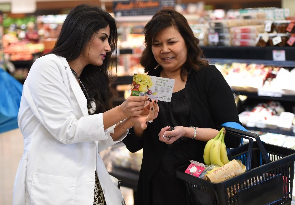 """Doctor's assitant Marina Sarwary (L) speaks with a shoper about organic food choices as part of the """"Shop with a Doc"""" program at a supermarket in Irvine, California (AFP Photo/Robyn Beck)"""
