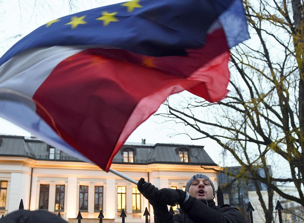 Protester waves the flags of Poland and the European Union in front of the Constitutional Court in Warsaw on December 3, 2015 (AFP Photo/Janek Skarzynski)