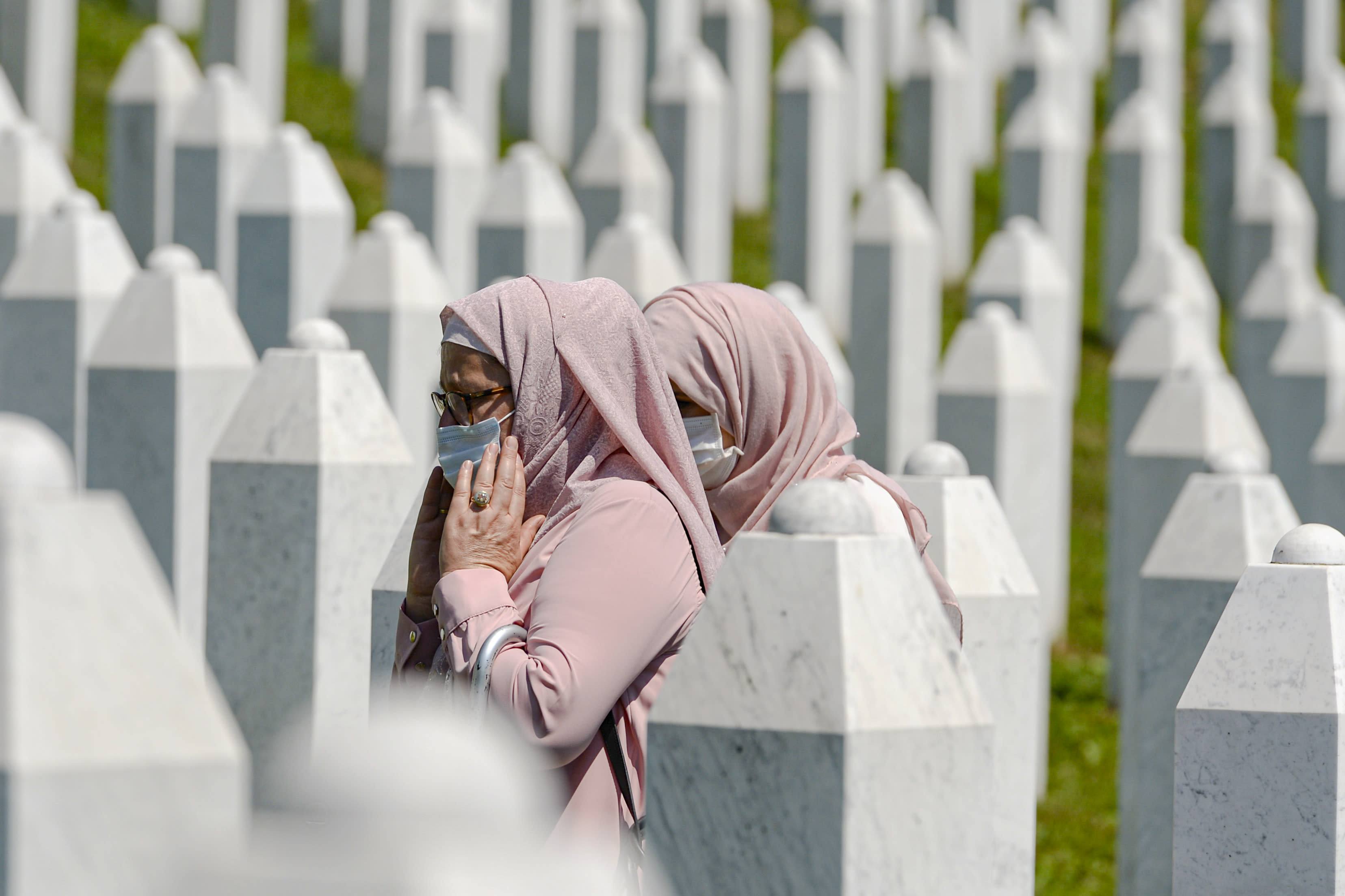 Women walk between grave stones in Potocari, near Srebrenica, Bosnia, Saturday, July 11, 2020. Mourners converged on the eastern Bosnian town of Srebrenica for the 25th anniversary of the country's worst carnage during the 1992-95 war and the only crime in Europe since World War II that has been declared a genocide. (AP Photo/Kemal Softic)