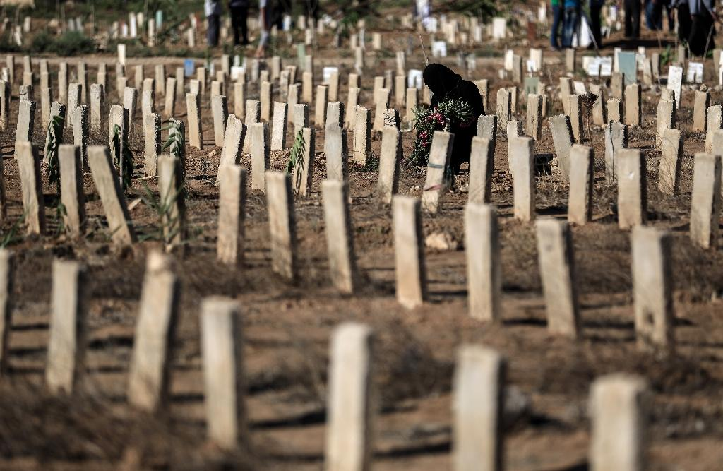A woman visits the grave of a relative in the town of Douma, east of Syria's capital Damascus, in July