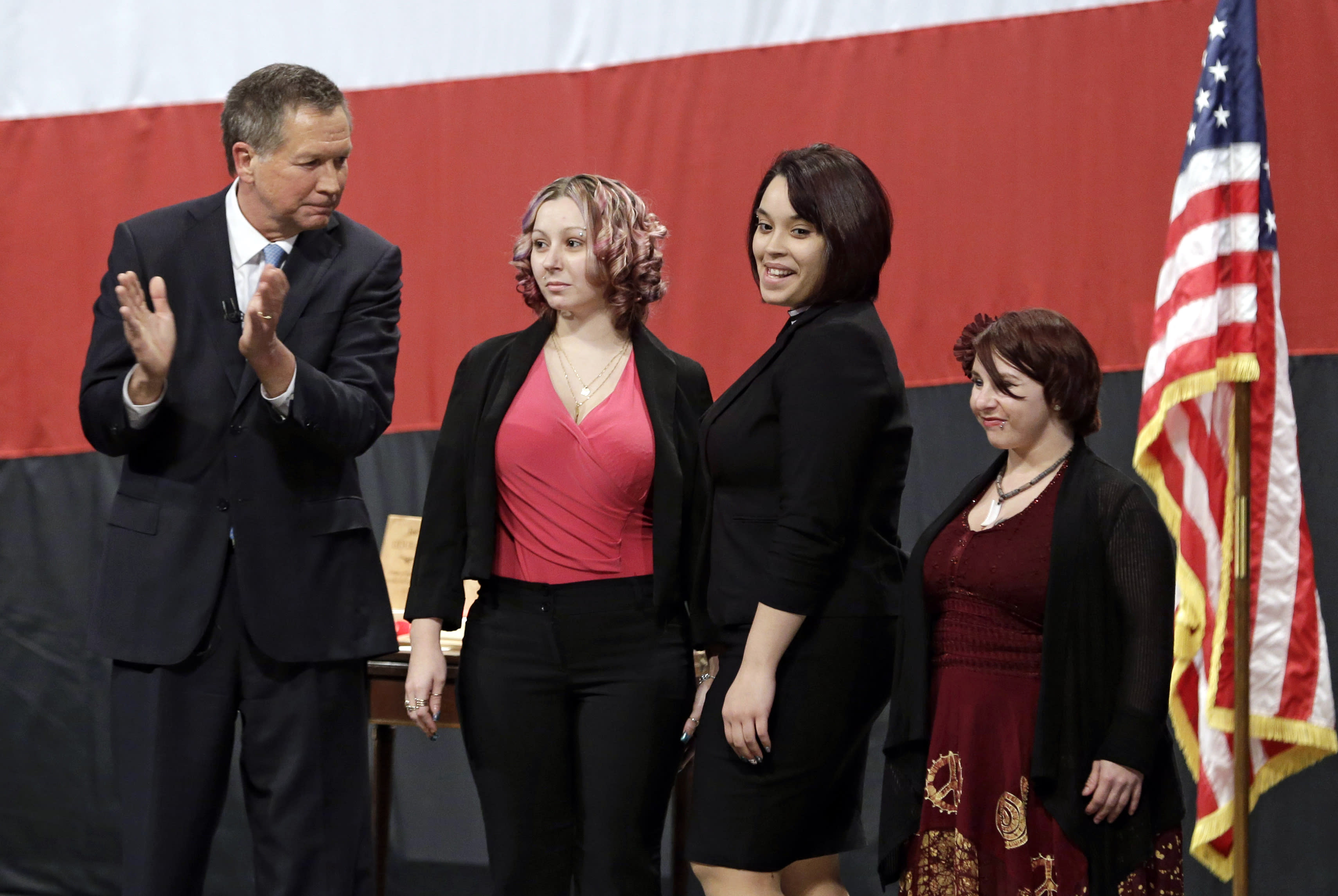 Ohio Gov. John Kasich, from left, introduces Amanda Berry, Gina DeJesus and Michelle Knight during his State of the State address at the Performing Arts Center Monday, Feb. 24, 2014, in Medina, Ohio. The three women, who survived a decades-long captivity in Cleveland before being rescued in May when Berry pushed her way through a door to freedom, received the Governor's Courage Award. (AP Photo/Tony Dejak)