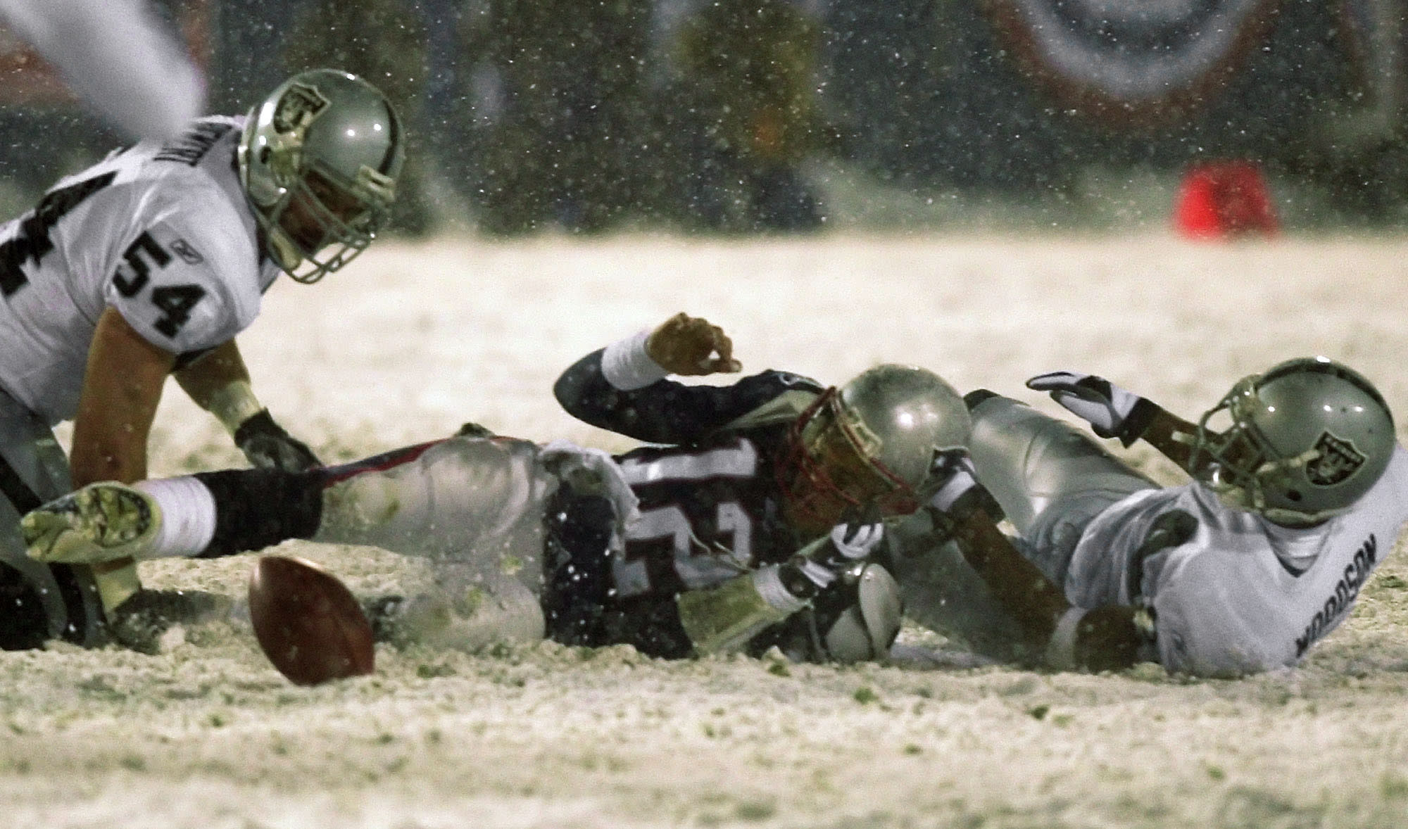 """File-New England Patriots quarterback Tom Brady (12) loses the ball after being brought down by Oakland Raiders' Charles Woodson, right, while Greg Biekert (54) moves to recover the ball in the fourth quarter of their AFC Division Playoff game in Foxboro, Mass. Saturday night, Jan. 19, 2002. The play was appealed, and the Patriots retained possession. Raiders coach Jon Gruden says opening this season at Carolina and then playing New Orleans on made him feel like he was in a time warp. His nostalgia is even more amplified this week against New England. It's been nearly two decades since he walked out of a snow-covered Foxboro Stadium on the wrong end of a 16-13 overtime loss to the Patriots in the infamous """"tuck rule"""" game during the 2001 playoffs. (AP Photo/Elise Amendola, File)"""
