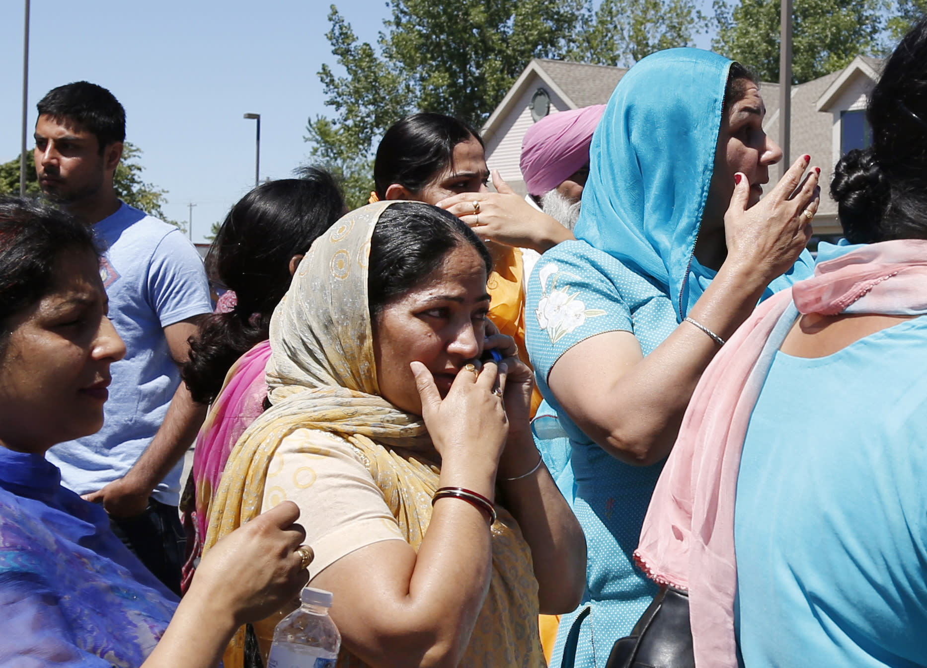 A woman uses a phone as people react outside the Sikh Temple of Wisconsin in Oak Creek, Wi, where a shooting took place Sunday, Aug 5, 2012. (AP Photo/Jeffrey Phelps)