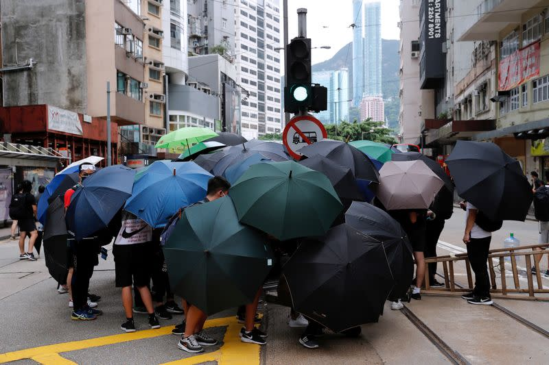 Anti-government protesters set up roadblocks under umbrellas during a march against Beijing's plans to impose national security legislation in Hong Kong