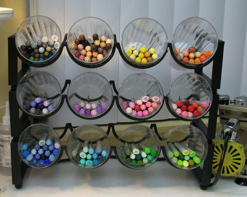 """<p>Wine racks can hold much more than a vintage merlot. <a href=""""http://mycasestudies.blogspot.com/2008/06/copic-stuff.html"""" rel=""""nofollow noopener"""" target=""""_blank"""" data-ylk=""""slk:Blogger Maureen Wong"""" class=""""link rapid-noclick-resp"""">Blogger Maureen Wong</a> nabbed stackable racks at Pier One, then filled them with inexpensive plastic cups from Walmart. (To secure the cups, she drilled two tiny holes in the bottom of each cup, then wired them to the back of the racks.) The result? Enviable marker storage—with the ability to add more as needed. (Credit: <a href=""""http://mycasestudies.blogspot.com/2008/06/copic-stuff.html"""" rel=""""nofollow noopener"""" target=""""_blank"""" data-ylk=""""slk:My Case Studies"""" class=""""link rapid-noclick-resp"""">My Case Studies</a>)</p>"""