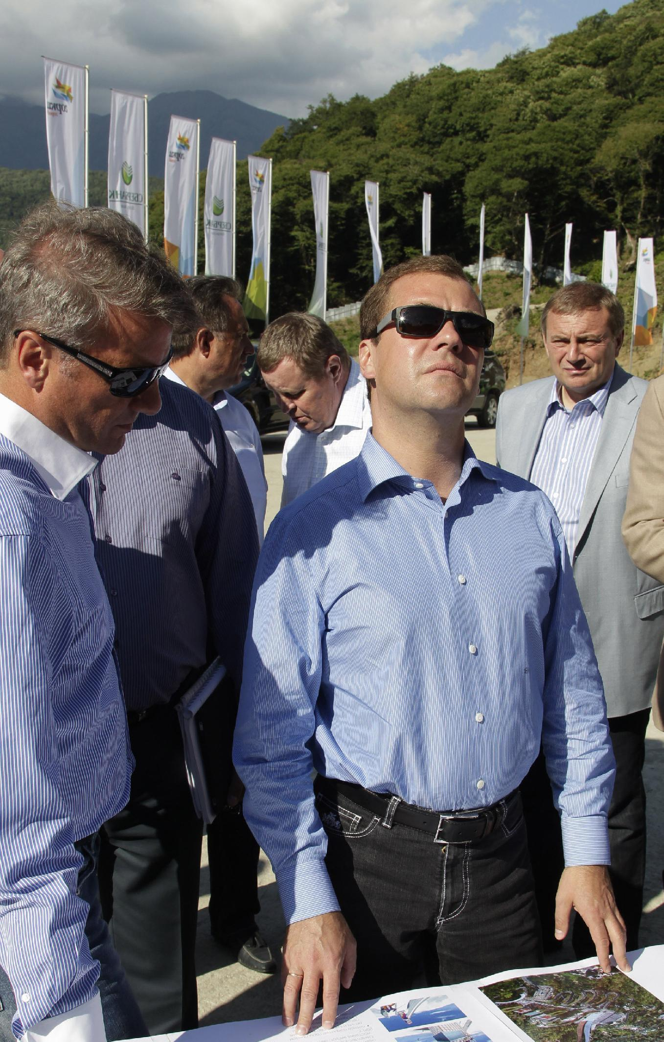 FILE - In this Tuesday, Aug. 23, 2011 file photo, then, Russian President Dmitry Medvedev and Sberbank President German Gref, left, visit a construction site of a skiing facility for the 2014 Sochi Winter Olympics, near the Black Sea resort of Sochi, southern Russia. The names of Russia's business powerhouses have taken over the mountains of Sochi, now the home of Potanin's slope, Gazprom's gondola lift and Sberbank's ski jump. These names, used by local residents and an army of construction workers, leave no doubt about who is paying for next year's Winter Games. (AP Photo/RIA Novosti, Mikhial Klimentyev, Presidential Press Service, File)