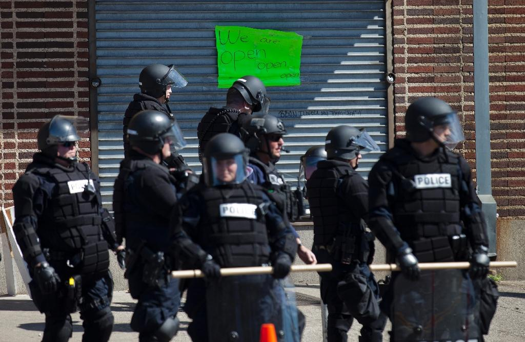 Policemen take a position outside a store at the Western District in Baltimore, Maryland on April 29, 2015