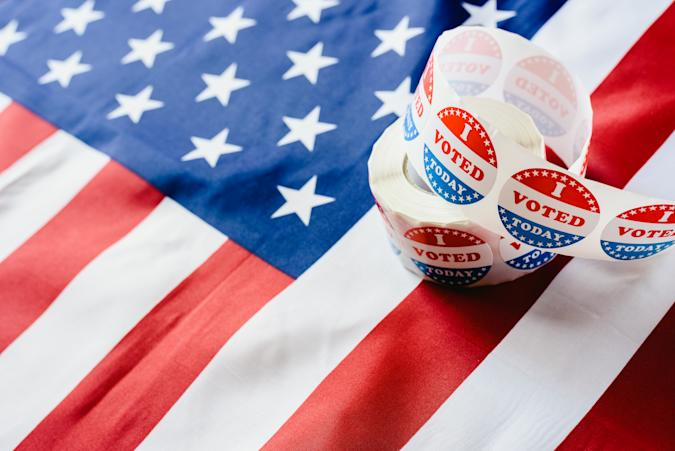 I vote today stickers roll, in US elections on American flag.