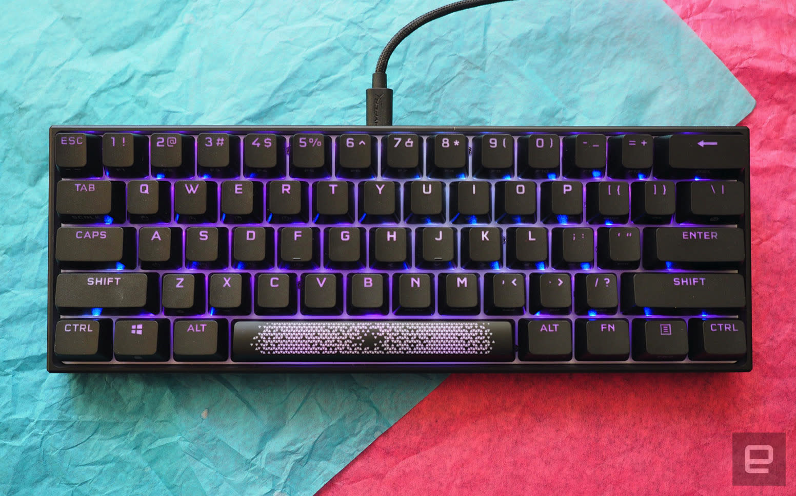 The Corsair K65 RGB Mini keyboard photographed on top of teal and red paper.