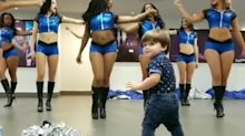 Toddler dances along with all-girl dance troupe