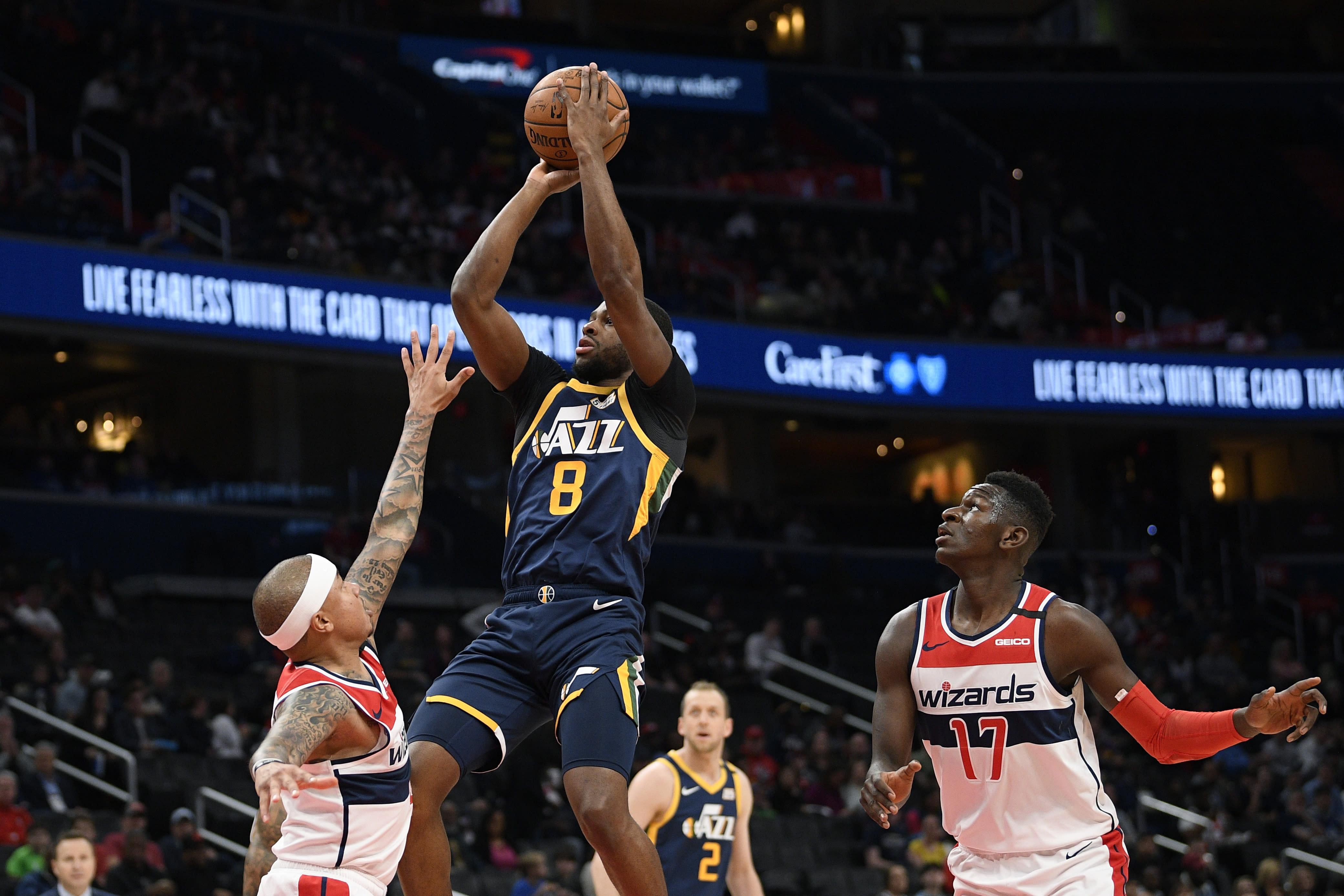 Utah Jazz guard Emmanuel Mudiay (8) shoots between Washington Wizards guards Isaiah Thomas, left, and Isaac Bonga (17) during the first half of an NBA basketball game, Sunday, Jan. 12, 2020, in Washington. (AP Photo/Nick Wass)
