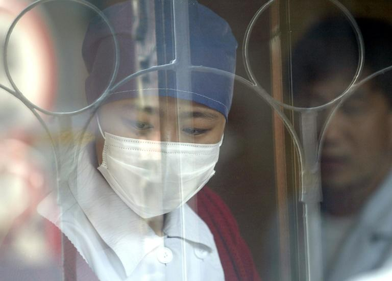 A Chinese nurse wears a mask as she attends to patients at a hospital in Beijing amid a SARS outbreak in April 2004