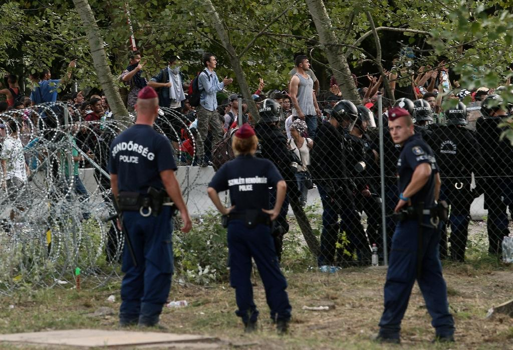 Hungarian riot police in Roszke secure the border as migrants attempt to break out from the no-man's land between the two countries at the Hungarian-Serbian border on September 16, 2015
