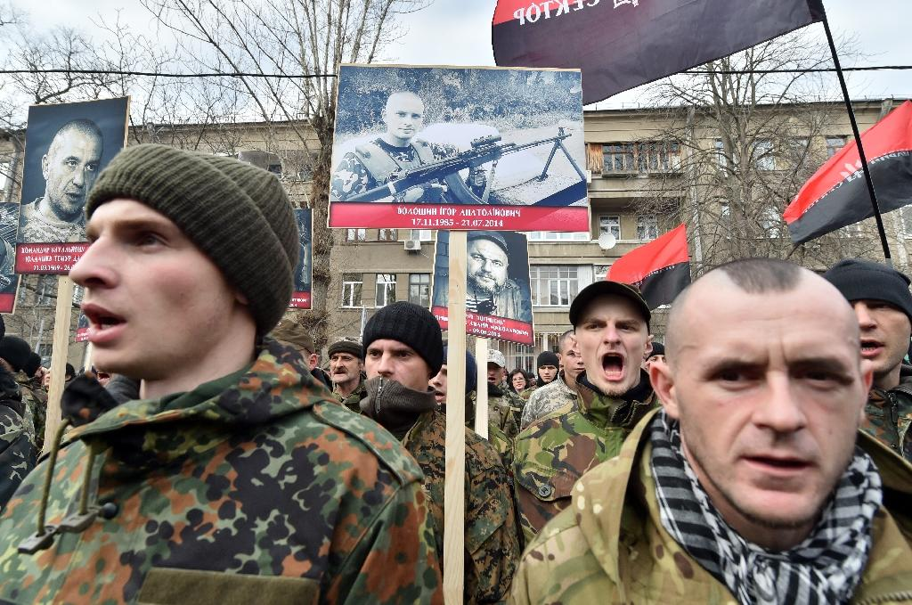 """Fighters from the Ukrainian volunteer battalions and activists of the Right Sector Party carry portraits of friends killed in the east of the country during a """"March of Truth, March of Rights """" in Kiev, on February 25, 2015 (AFP Photo/Sergei Supinsky)"""