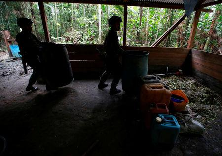 Colombian anti-narcotics policemen lift barrels in a cocaine lab, which, according to the police, belongs to criminal gangs in rural area of Calamar in Guaviare state, Colombia, August 2, 2016. REUTERS/John Vizcaino