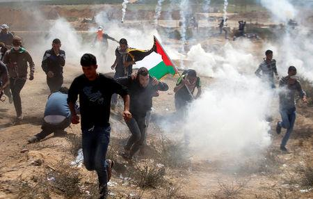 Palestinians run from tear gas fired by Israeli troops during clashes at the Israel-Gaza border at a protest demanding the right to return to their homeland, east of Gaza City April 6, 2018. REUTERS/Mohammed Salem