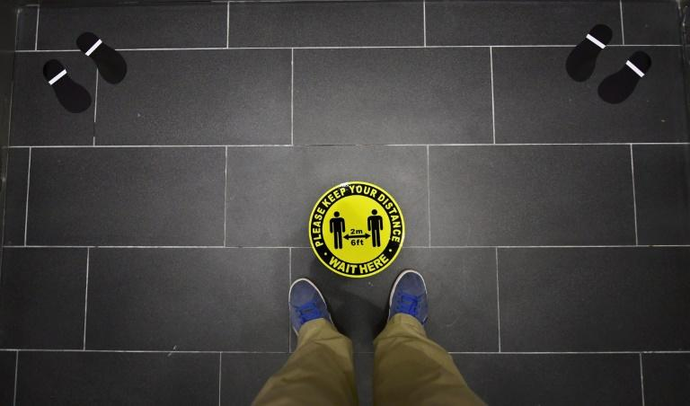 Foot markings and a coronavirus social distance reminder are seen on the floor of an elevator in an office building in Hollywood, California on July 7, 2020 (AFP Photo/Frederic J. BROWN)