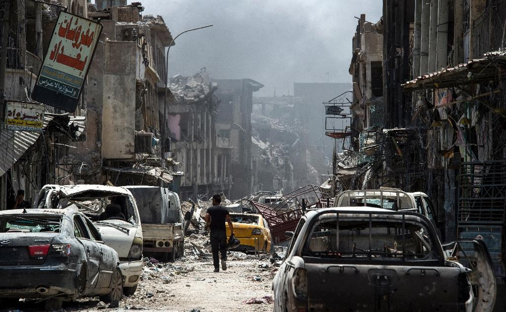 A man walks by destroyed vehicles in a street in the Old City of Mosul on July 2, 2017, during the offensive to retake the city from Islamic State (IS) group fighters (AFP Photo/Fadel SENNA)