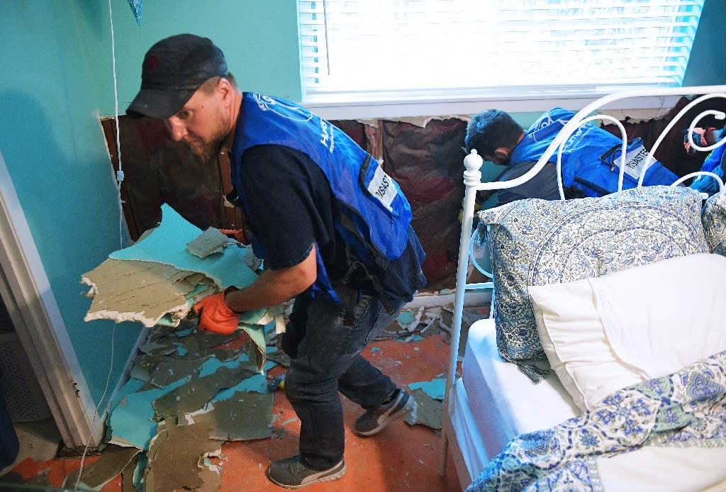 Ahmadiyya Muslim Youth Association members remove flood damaged drywall from a home in the Westbury neighborhood of southwest Houston, Texas (AFP Photo/Mandel NGAN)