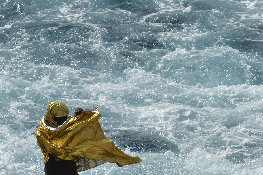 A migrant wrapped in a survival foil blanket stands aboard the Topaz Responder ship, run by Maltese NGO Moas and the Italian Red Cross, while sailing to the port of Vibo Valentia, southern Italy, after rescue missions off the Libyan coast (AFP Photo/Andreas Solaro)