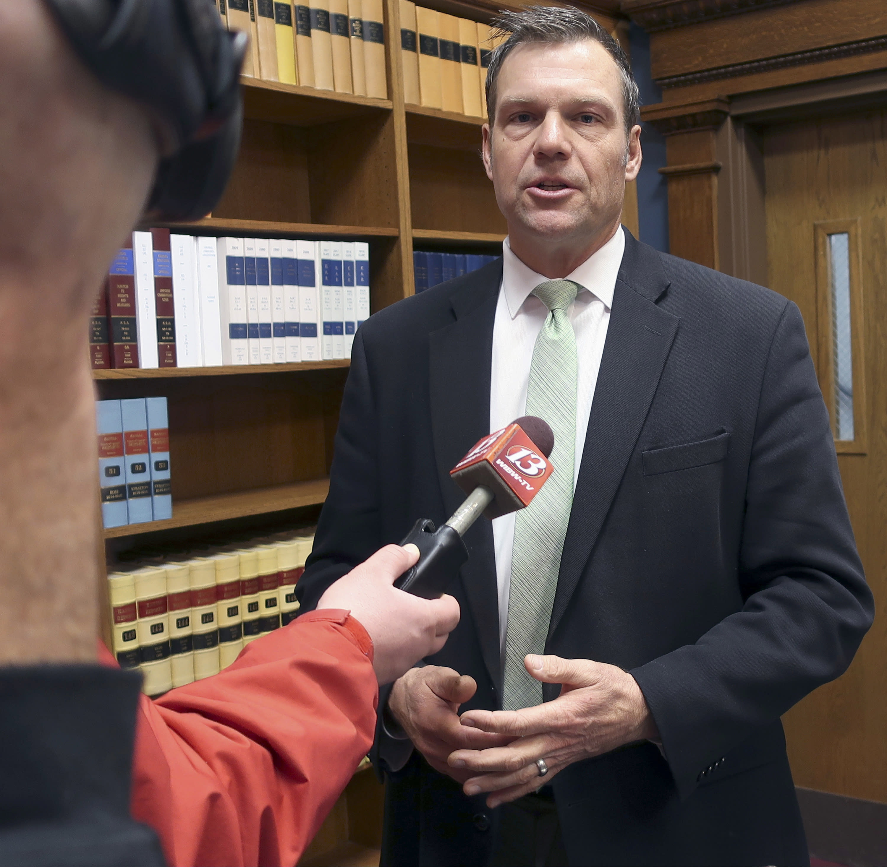FILE - In this Nov. 30, 2018 file photo, then Kansas Secretary of State Kris Kobach responds to questions from reporters in Topeka, Kan. Schmidt announced Tuesday, June 2, 2020, that he will appeal a 10th U.S. Circuit Court of Appeals decision in April that said the state could not enforce a proof-of-citizenship law. An appeals-court panel said the law violated the U.S. Constitution's guarantee of equal legal protection as well as a federal voter registration law.(AP Photo/John Hanna, File)