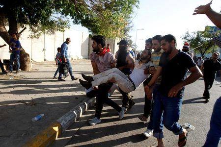 Anti-government protesters carry a man injured during the storming of Baghdad's Green Zone in Iraq May 20, 2016. REUTERS/Khalid al Mousily