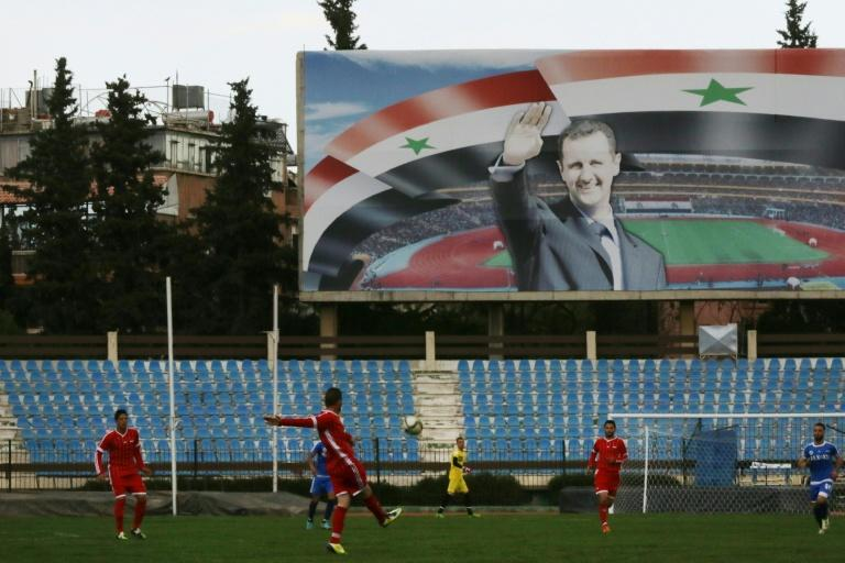 A poster of Syrian President Bashar al-Assad looms large during a March 2016 league match between Latakia's Hutteen (blue) and Hama's Taliya at Tishreen stadium in Damascus