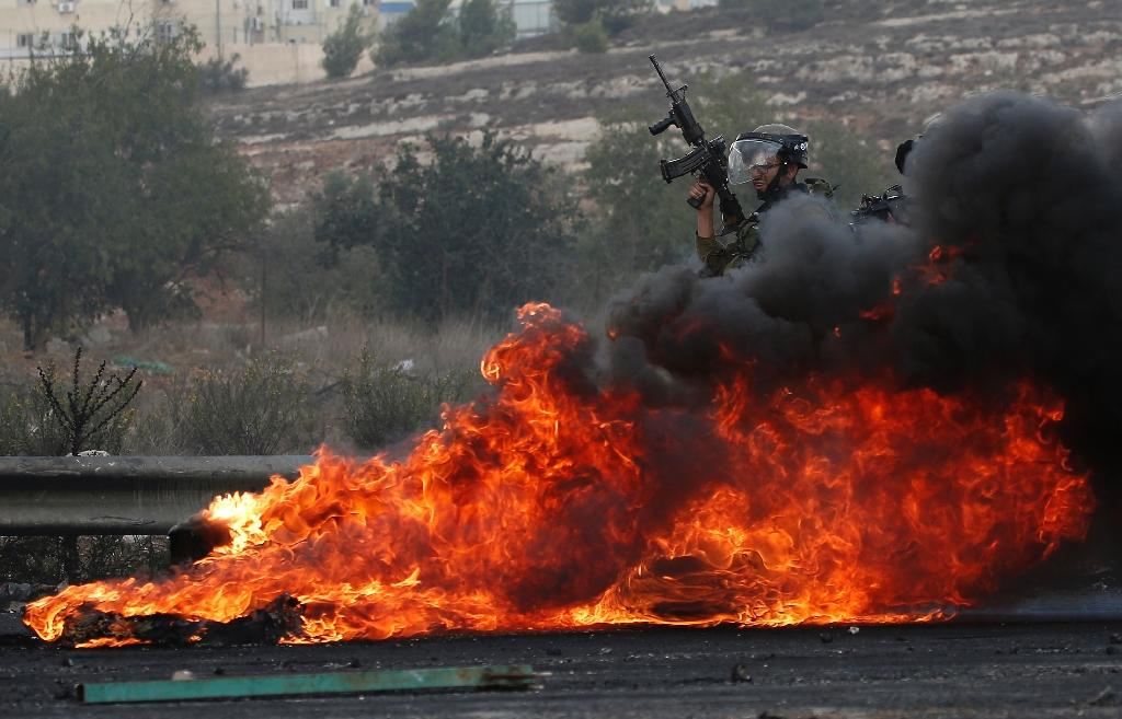 Israeli security forces stand behind burning tires during clashes with Palestinians in Beit El, near the West Bank city of Ramallah on October 9, 2015 (AFP Photo/Abbas Momani)