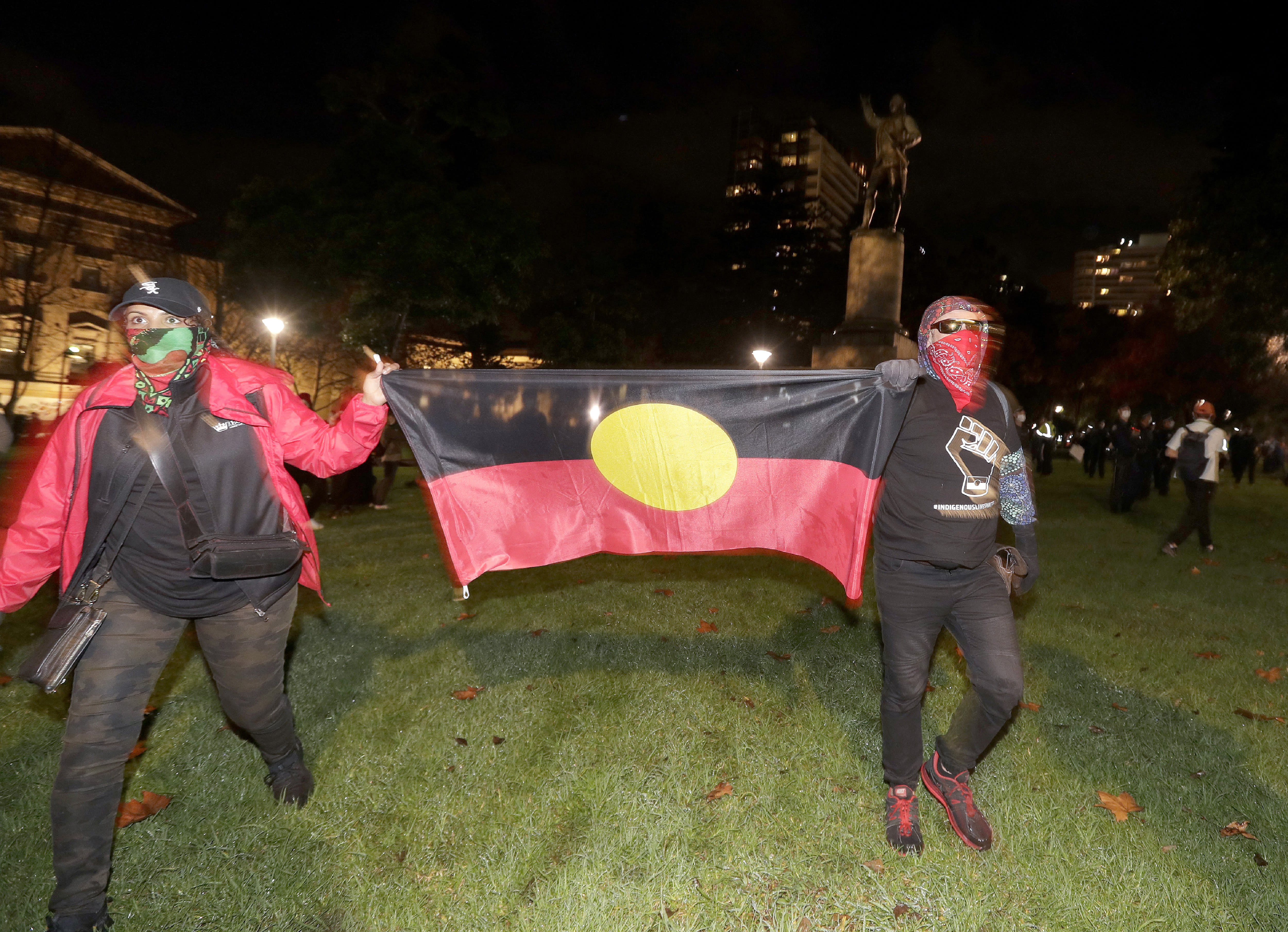 Protestoers carry an Aboriginal flag as the walk past a statue of British explorer James Cook in Sydney, Friday, June 12, 2020, to support U.S. protests over the death of George Floyd. Hundreds of police disrupted plans for a Black Lives Matter rally but protest organizers have vowed that other rallies will continue around Australia over the weekend despite warnings of the pandemic risk. (AP Photo/Rick Rycroft)