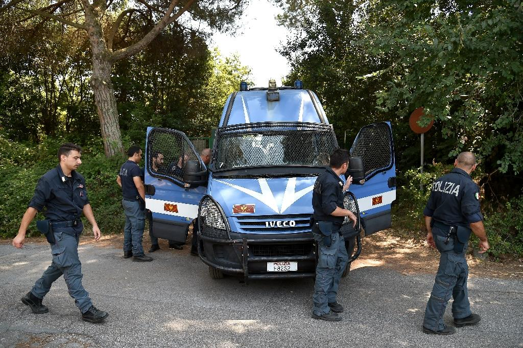 Police on guard at Casale San Nicola, north of Rome, as hundreds of local residents supported by members of extreme-right group CasaPound demonstrated against the arrival of twenty migrants on July 17, 2015 (AFP Photo/Alberto Pizzoli)