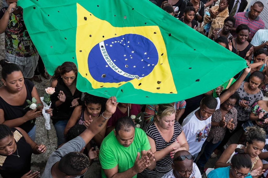 Relatives and friends carry a Brazilian flag with 50 holes as they mourn Wilton Esteves Domingos Junior, 20, killed with four other friends last Satuday by policemen who shot 50 times at their car, in Rio de Janeiro, on November 30, 2015 (AFP Photo/Christophe Simon)