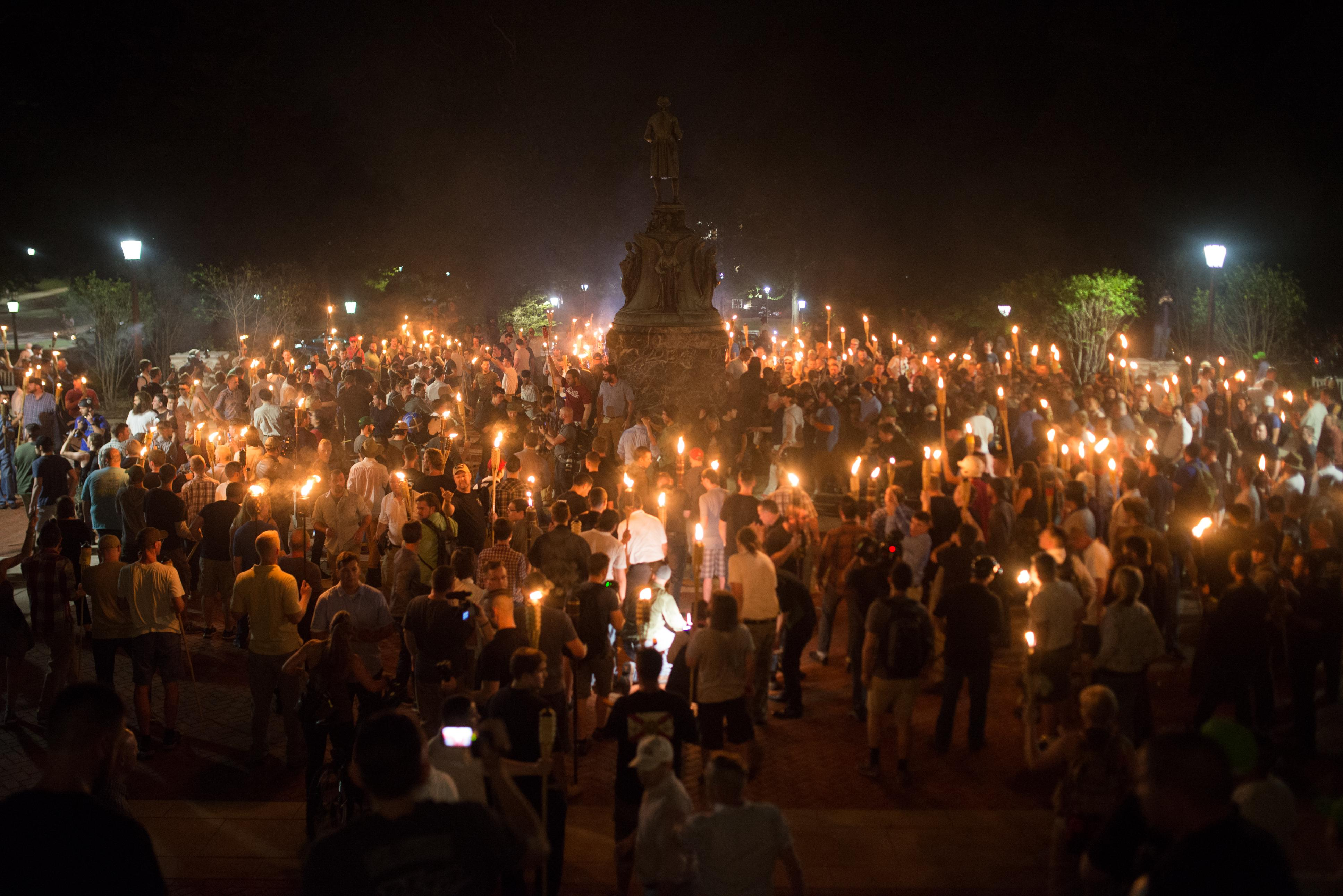 <p>Neo-Nazis, Alt-Right, and White Supremacists encircle counter protestors at the base of a statue of Thomas Jefferson after marching through the University of Virginia campus with torches in Charlottesville, Va., on Aug. 11, 2017. (Photo: Zach D Roberts/NurPhoto via Getty Images) </p>