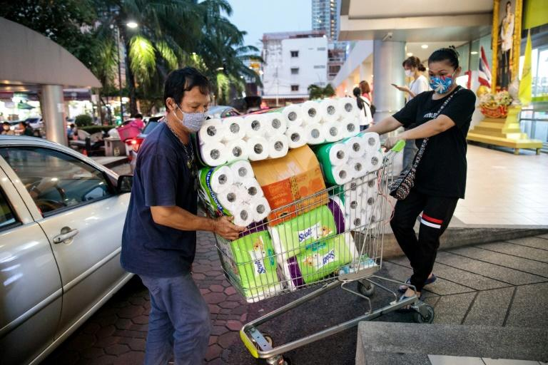 People wearing face masks amid concerns over the COVID-19 coronavirus push a shopping cart full of toilet paper and kitchen rolls at a supermarket in Bangkok on March 16, 2020 (AFP Photo/Jack Taylor)