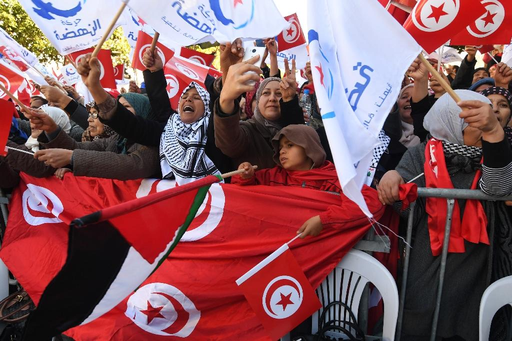 Tunisians wave their national flag and the flag of the Ennahda Islamist party as they gather on Habib Bourguiba Avenue in Tunis on January 14, 2018 to mark the seventh anniversary of the uprising that launched the Arab Spring (AFP Photo/FETHI BELAID)