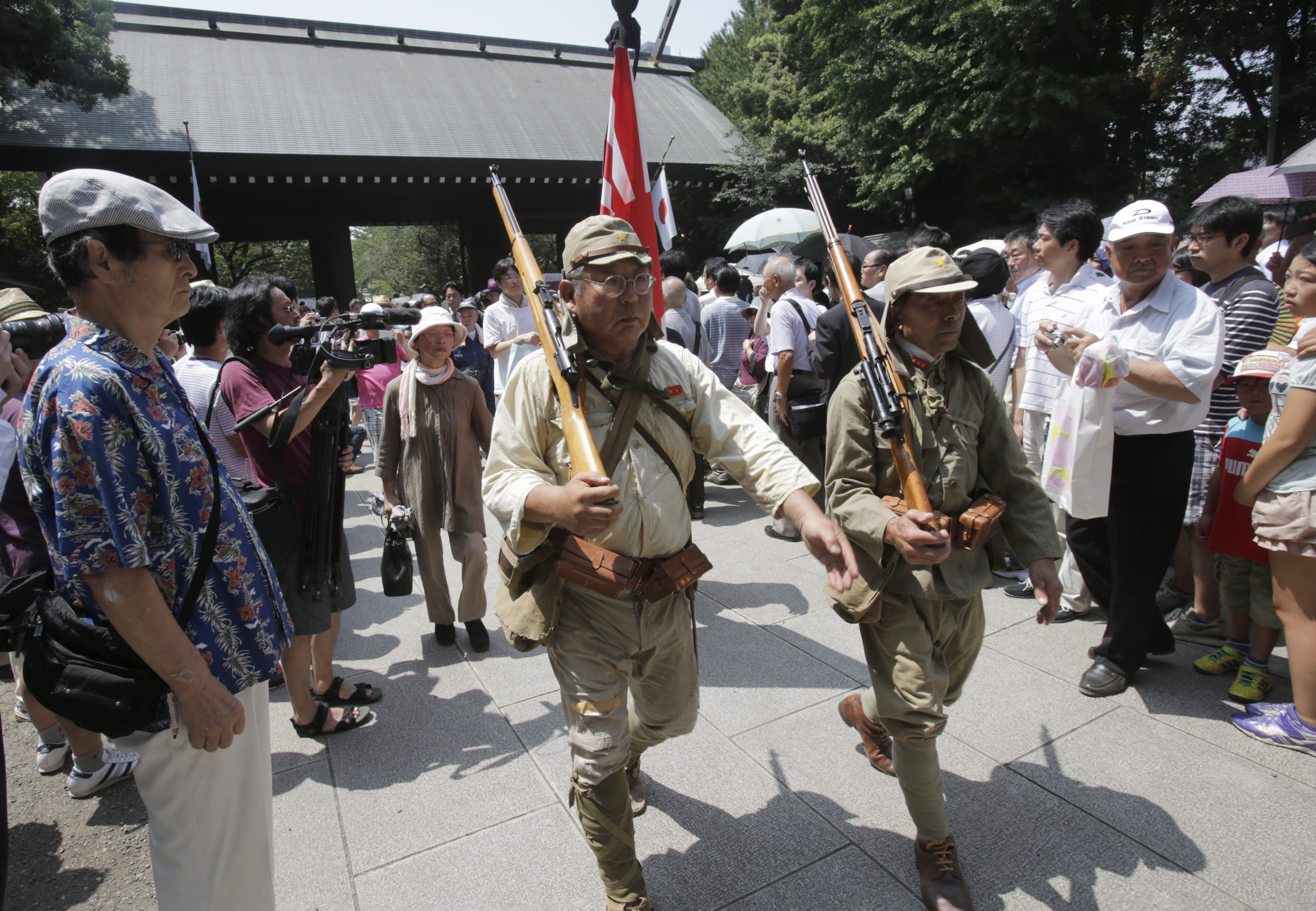 Japanese men clad in outdated military costume march in to pay respects to the nation's war dead at the Yasukuni Shrine in Tokyo Thursday, Aug. 15, 2013. Japan marked the 68th anniversary of its surrender in World War II with somber ceremonies Thursday and visits by senior politicians to the shrine honoring 2.5 million war dead that remains a galling reminder of colonial and wartime aggression. (AP Photo/Shizuo Kambayashi)
