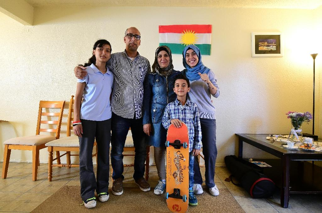 Syrian refugee family of Ammar Kawkab (2nd L), his wife Leila (C) and children Noor (L), Aya (R) and Hamza with his skateboard, pose for a photo at their apartment in San Diego, on August 31, 2016 (AFP Photo/Frederic J. Brown)