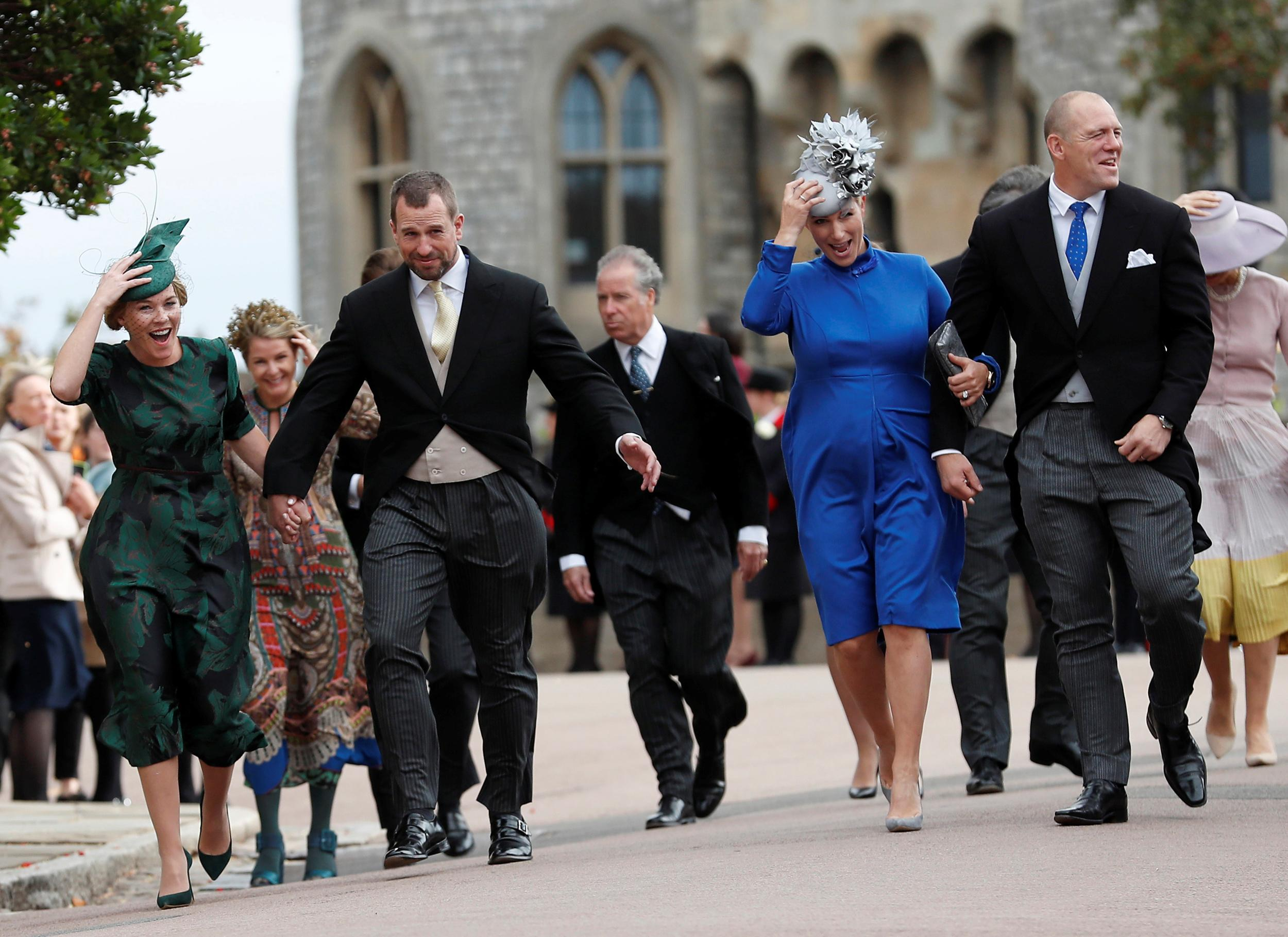 Autumn Phillips, with Peter Phillips, Zara Phillips, and Mike Tindal, from left, hold onto their hats as they arrive for the wedding of Princess Eugenie of York and Jack Brooksbank in St George's Chapel, Windsor Castle, Windsor, Britain, October 12, 2018. Alastair Grant/Pool via REUTERS