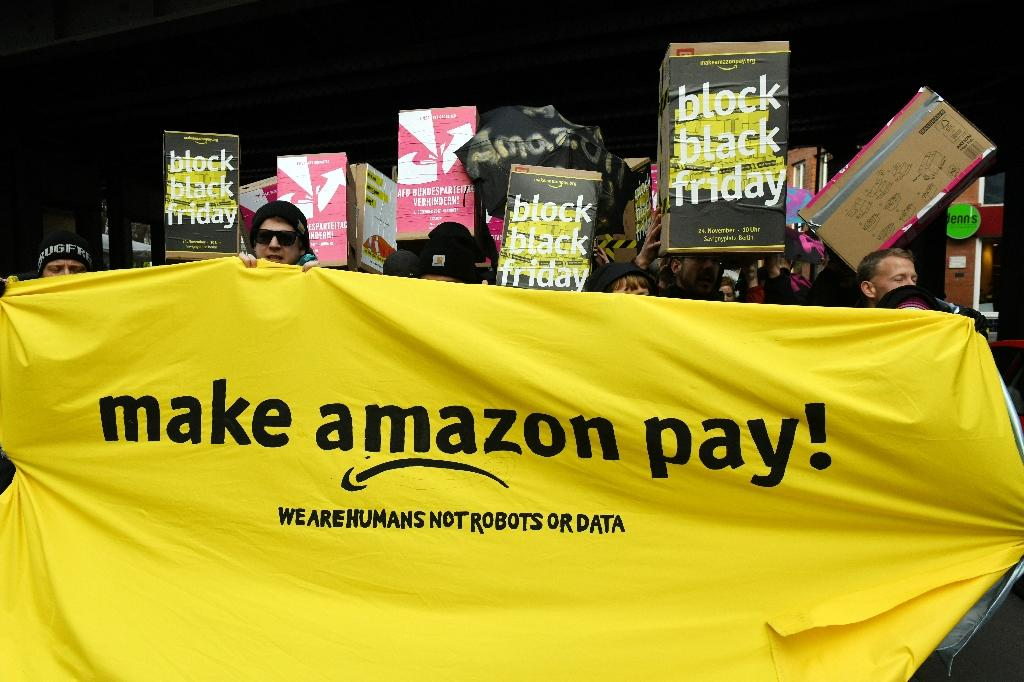 Protesters hold banners and placards during a demonstration demanding better pay and conditions at the online retailer Amazon