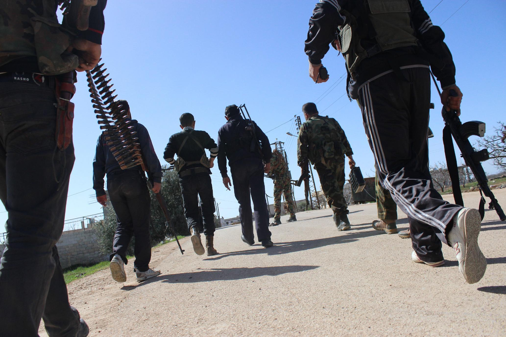 Rebel fighters make their way to the front-line in the Syrian village of Morek on March 7, 2014